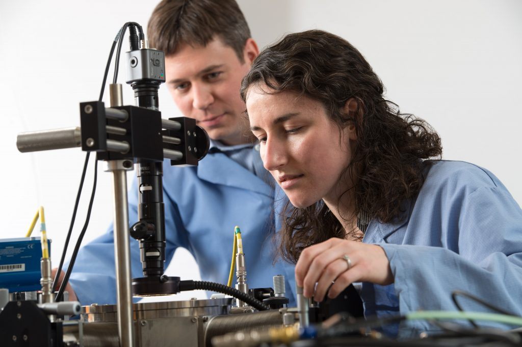 Chemistry graduate student Taylor S. Teitsworth (with James Cahoon, left) uses a cryogenic probe station, which allows her to perform electrical measurements on semiconductor nanowire materials at very low temperatures. (photo by Steve Exum)